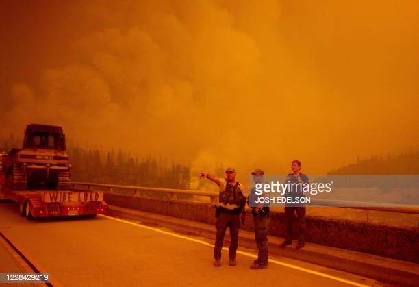 Law enforcement and fire personnel wait on the Enterprise Bridge to enter an area encroached by fire during the Bear fire, part of the North...