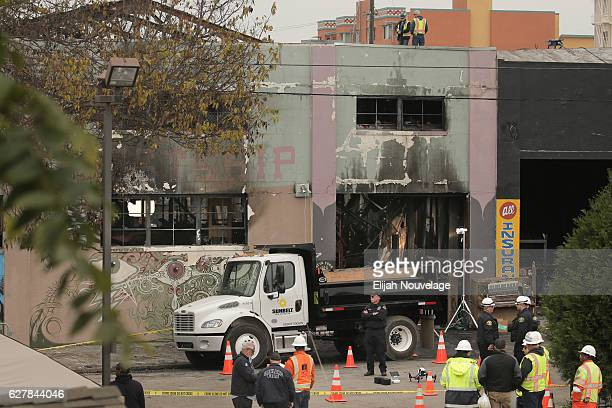 Law enforcement and firefighters are seen at the site of a warehouse fire that has claimed the lives of at least thirtysix people on December 5 2016...