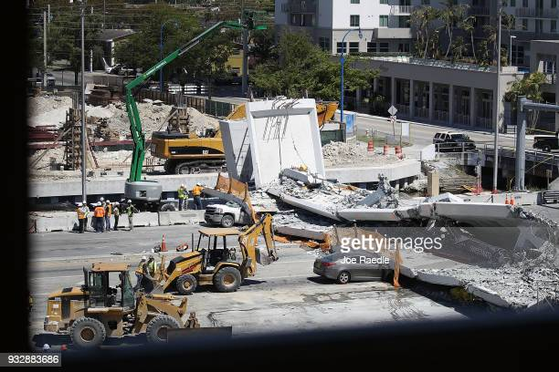 Law enforcement and members of the National Transportation Safety Board investigate the scene where a pedestrian bridge collapsed a few days after it...