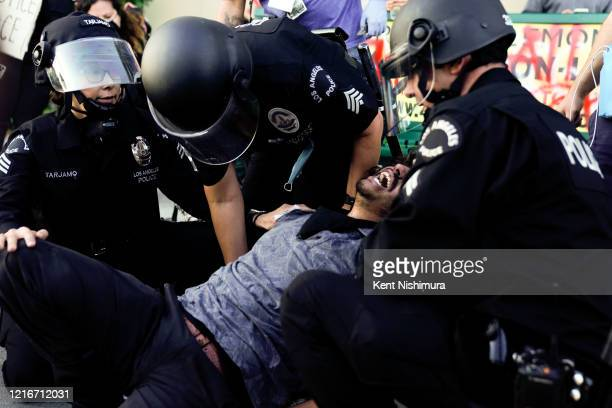 Law enforcement carry a man after he was cuffed in the Fairfax District on Saturday, May 30, 2020 in Los Angeles, CA. Protests erupted across the...