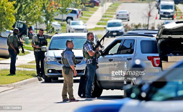 Law enforcement gather as a home is searched for the suspect in a shooting at Timeberview High School on October 6, 2021 in Arlington, Texas....