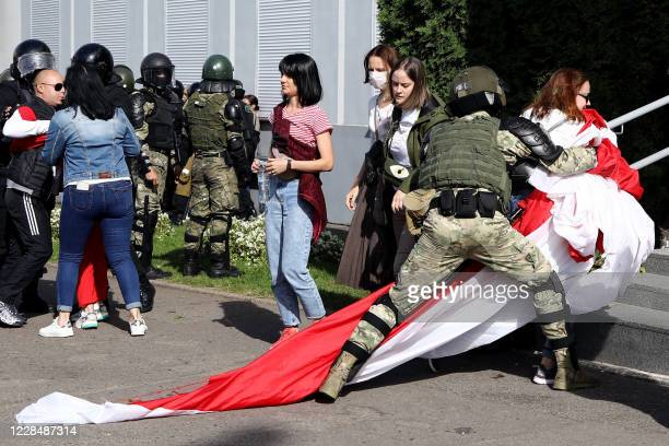 TOPSHOT A law enforcement officer detains a woman with a huge former whiteredwhite flag of Belarus during a rally to protest against the presidential...