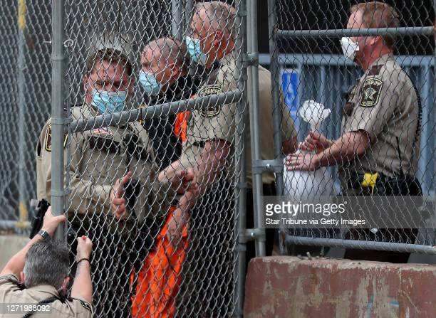 Law enforcement officer goes down while opening a gate for fired Minneapolis police officer Derek Chauvin as fellow officers escorted Chaurin from...