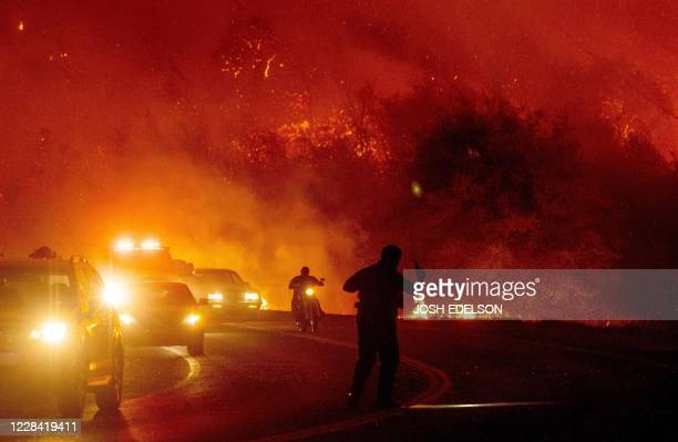 Law enforcement officer guides evacuees down a road surrounded by fire at the Bear fire in Oroville, California on September 9, 2020. - Dangerous dry...