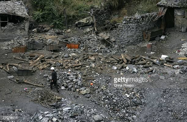 A law enforcement officer inspects after an illegal coal mine was demolished by explosives in Fangshan District on September 28 2007 in suburban...