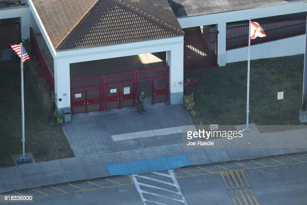 A law enforcement officer stands at the front door of the Marjory Stoneman Douglas High School after a shooting at the school that reportedly killed...