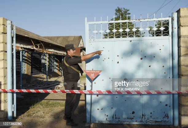 A law enforcement officer stands by the gate of a cordoned off house due to an unexploded shell threat in the village of Agdam in Tovuz district...