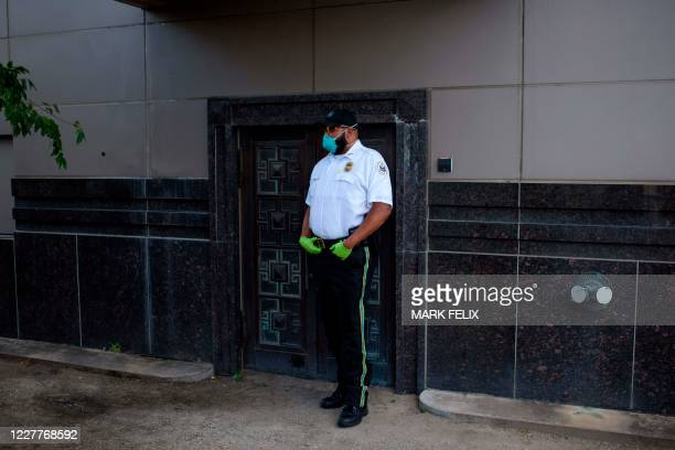 A US law enforcement officer stands guard at a back door where US law enforcement entered the Chinese consulate in Houston July 24 after the US State...