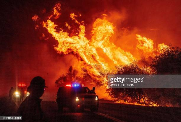 Law enforcement officer watches flames launch into the air as fire continues to spread at the Bear fire in Oroville, California on September 9, 2020....
