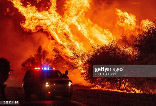 Law enforcement officer watches flames launch into the air as fire continues to spread during the Bear fire in Oroville, California on September 9,...