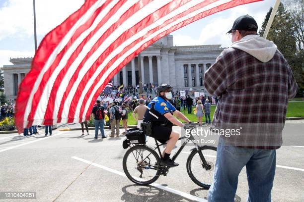 A law enforcement officer wearing a mask rides a bike past a demonstrator with a flag during a 'Hazardous Liberty Defend the Constitution' rally at...