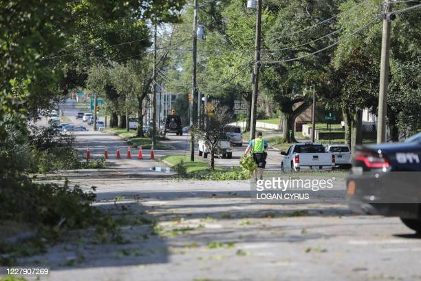 A law enforcement officer with the Wilmington Police Department works to clear tree branch debris from a main street after Hurricane Isaias made...