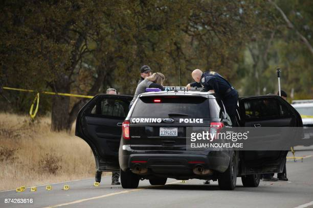 Law enforcement officers and a crime scene photographer examine a police vehicle that was involved in a shooting in the morning on November 14 in...