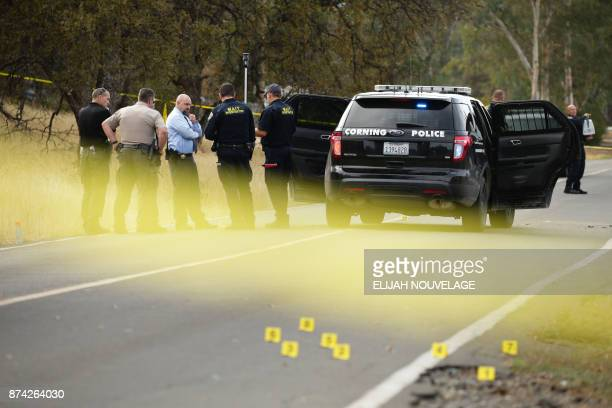 Law enforcement officers and investigators converse near a police vehicle that was involved in a shooting on November 14 in Rancho Tehama California...