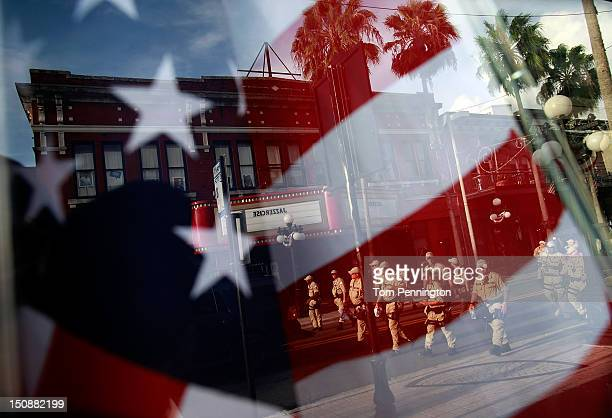 Law enforcement officers are reflected in a storefront window as they clear a downtown street during an organized protest on the first full day of...