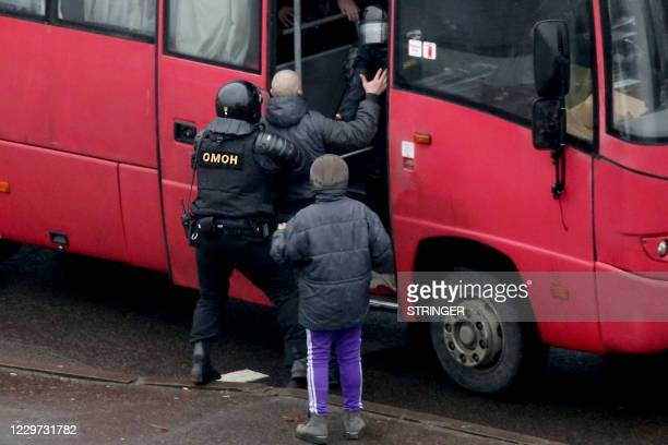 Law enforcement officers detain a man as opposition supporters rally to protest against police violence and Belarus' presidential election results in...