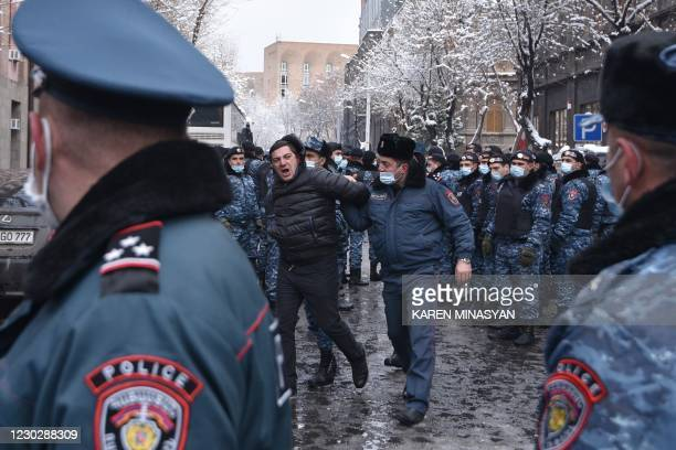 Law enforcement officers detain an opposition supporter during a rally to demand the resignation of Prime Minister Nikol Pashinyan over a...