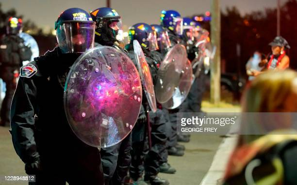 Law enforcement officers in riot gear block a street outside the venue where the vice presidential debate was taking place in Salt Lake City, Utah on...