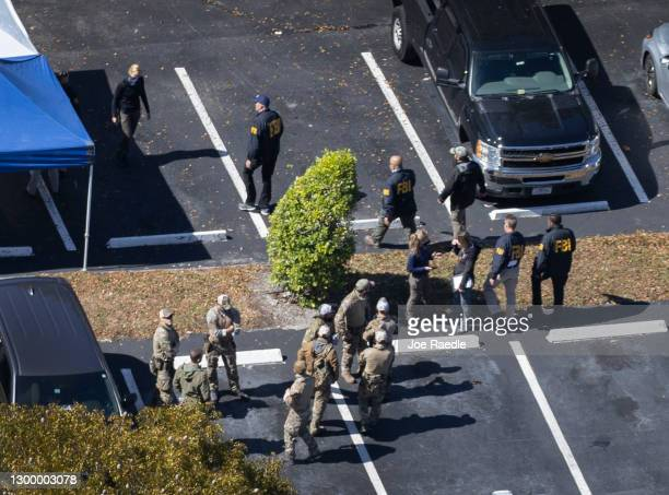 Law enforcement officers investigate the scene where two FBI agents were killed and others shot as they served a warrant in a child exploitation case...