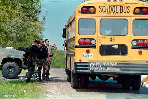 Law enforcement officers manning a roadblock on April 02 1993 near the Branch Davidian religious compound wave to students as they pass through on...