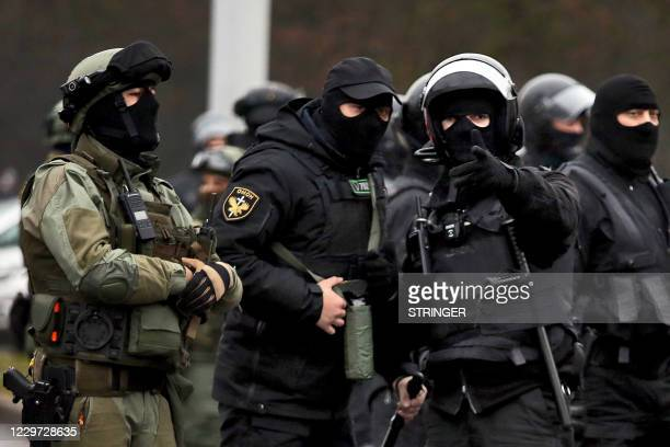 Law enforcement officers patrol a street as opposition supporters rally to protest against police violence and Belarus presidential election results...