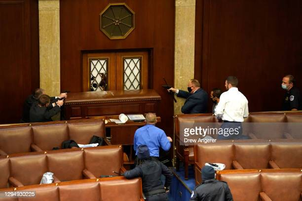 Law enforcement officers point their guns at a door that was vandalized in the House Chamber during a joint session of Congress on January 06, 2021...