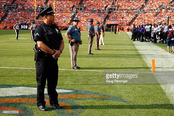 Law enforcement officers provide security on the field during a break in the action between the Baltimore Ravens and the Denver Broncos at Sports...