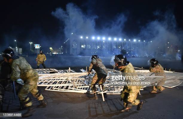 Law enforcement officers remove a barricade set up by protesters during a rally against the results of a parliamentary vote in Bishkek on October 5,...