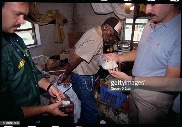 Law enforcement officers search through a crack house following a raid The crack house was being run by 82yearold Frank Wilcher