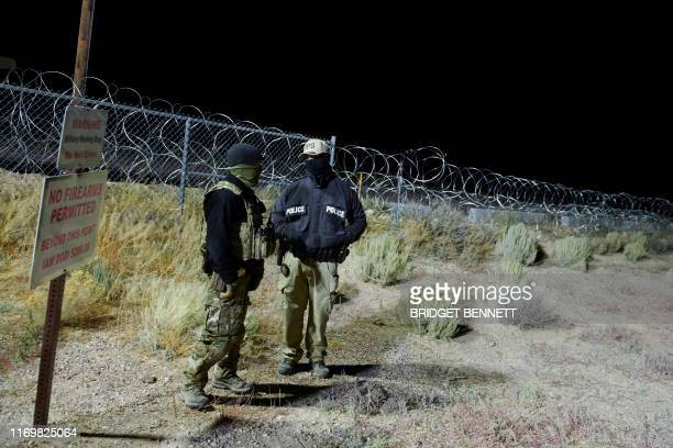 Law enforcement officers stand guard at a fence in an area attendees gathered to storm Area 51 at an entrance near Rachel Nevada on September 20 2019...