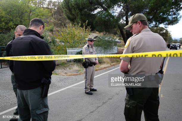 Law enforcement officers stand near one of many crime scenes after a shooting on November 14 in Rancho Tehama California Four people were killed and...