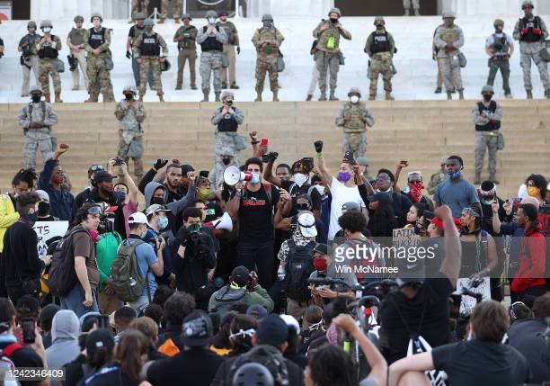 Law enforcement officers stand on the steps of the Lincoln Memorial as demonstrators protest against police brutality and the death of George Floyd...