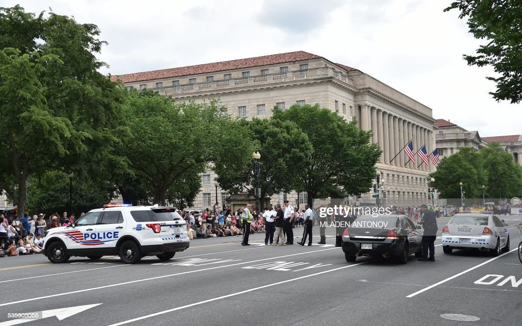 Law enforcement officers stop the Memorial Day Parade on Constitution Avenue during a security lockdown of the White House grounds on May 30, 2016 Washington DC. / AFP / MLADEN