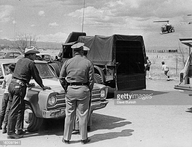 MAR 30 1968 MAR 31 1968 Law Enforcement officers watch as Helicopter comes in for a Landing at Search Headquarters Colorado Bureau of Investigation...