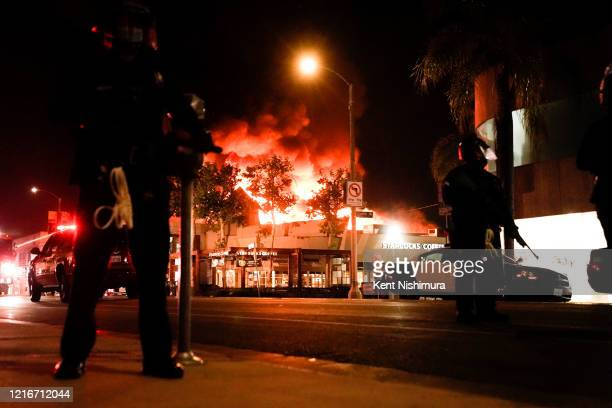 Law enforcement officers with a structure ablaze int he background in the Fairfax District on Saturday, May 30, 2020 in Los Angeles, CA. Protests...