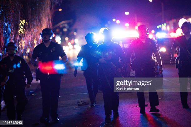 Law enforcement officers yell disperse to people not respecting the curfew as protestors in the Fairfax District flee on Saturday, May 30, 2020 in...