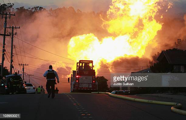 A law enforcement official runs towards a massive fire in a residential neighborhood September 9 2010 in San Bruno California A massive explosion...