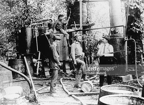 Law enforcement official stand near illegal alcohol production equipment captured during a 'moonshine' raid during America's prohibition period in...