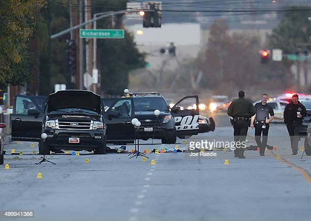 Law enforcement officials continue their investigation around the Ford SUV vehicle that was the scene where suspects of the shooting at the Inland...