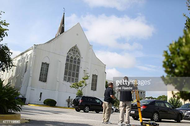 Law enforcement officials continue their investigation in the parking lot of the Emanuel African Methodist Episcopal Church after a mass shooting at...