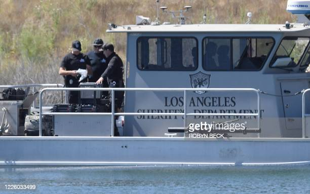 Law enforcement officials gather at the boating dock of Lake Piru in the Los Padres National Forest Ventura County California on July 10 as the...