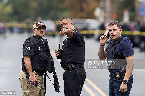 Law enforcement officials gather at the site where Ahmad Khan Rahami who was wanted in connection to Saturday night's bombing in Manhattan was...
