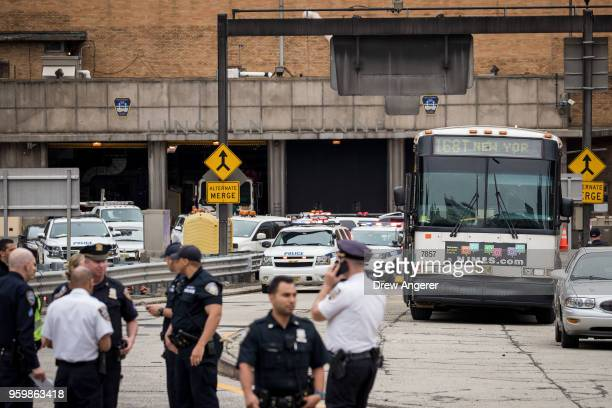 Law enforcement officials gather near the scene of a New Jersey Transit bus that was involved in a morning crash near the Manhattan entrance to the...