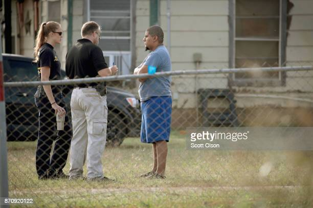 Law enforcement officials interview a resident as they continue their investigation of the shooting at the First Baptist Church of Sutherland Springs...
