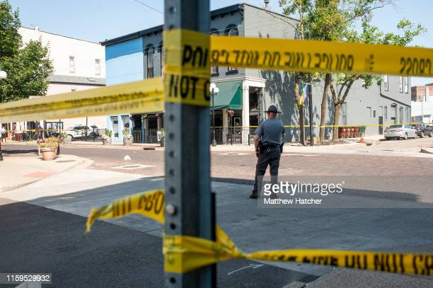 Law enforcement officials investigate the scene where a gunman opened fire on a crowd of people over night on Fifth Avenue in the Oregon District on...