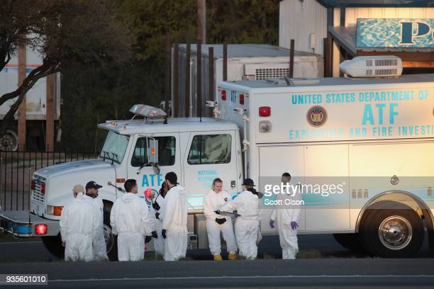 Law enforcement officials search for evidence at the location where the suspected package bomber was killed in suburban Austin on March 21 2018 in...