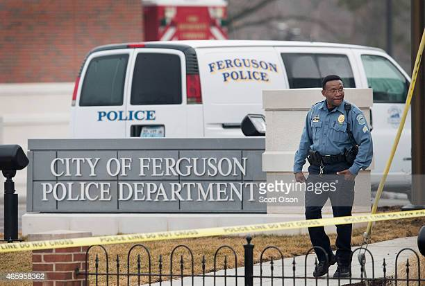 Law enforcement officials secure the crime scene and continue to search for evidence outside the police station after two officers were shot and...