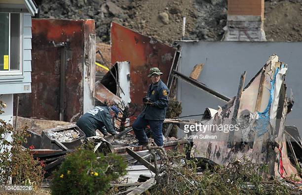 Law enforcement officials sift through rubble at the site of a home destroyed by a deadly gas main explosion September 13, 2010 in San Bruno,...