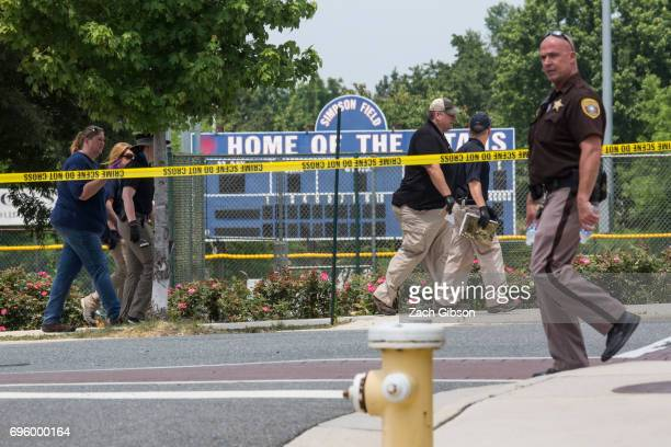 Law enforcement officials work near Eugene Simpson Field the site where a gunman opened fire June 14 2017 in Alexandria Virginia Multiple injuries...