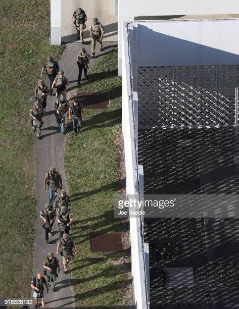 Law enforcement personel work the scene at the Marjory Stoneman Douglas High School after a shooting at the school that reportedly killed and injured...